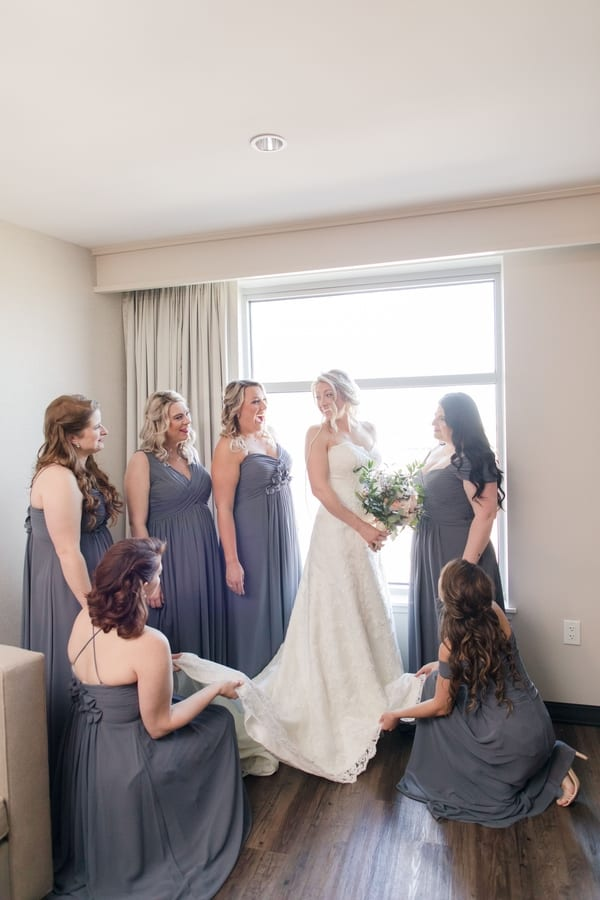 bride holding her bridal bouquet while standing by a window, surrounded by her bridal party