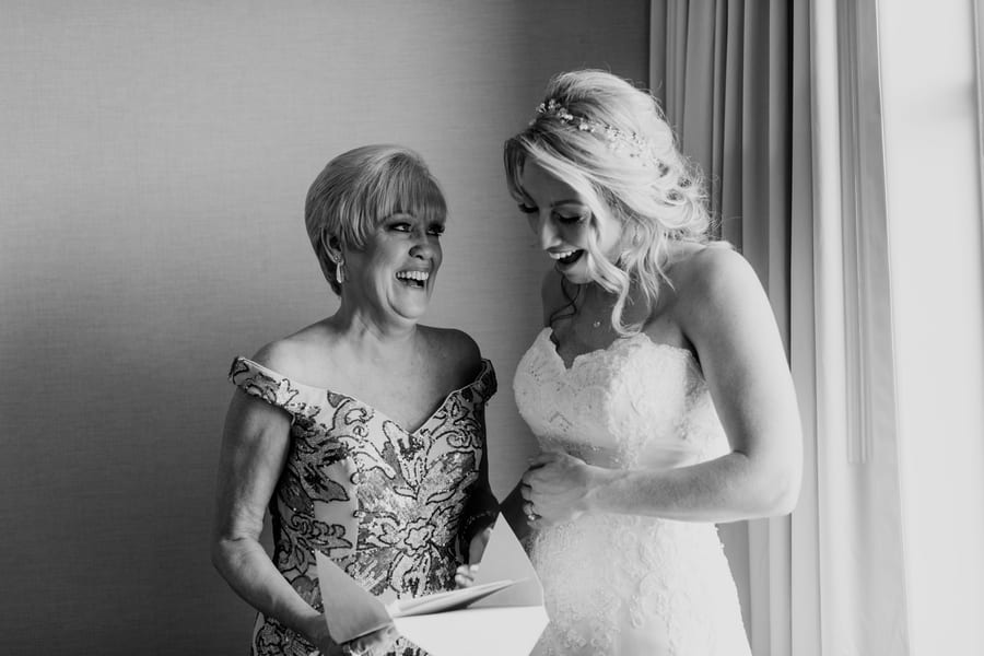 black and white candid photo of bride and her mom opening a gift, laughing