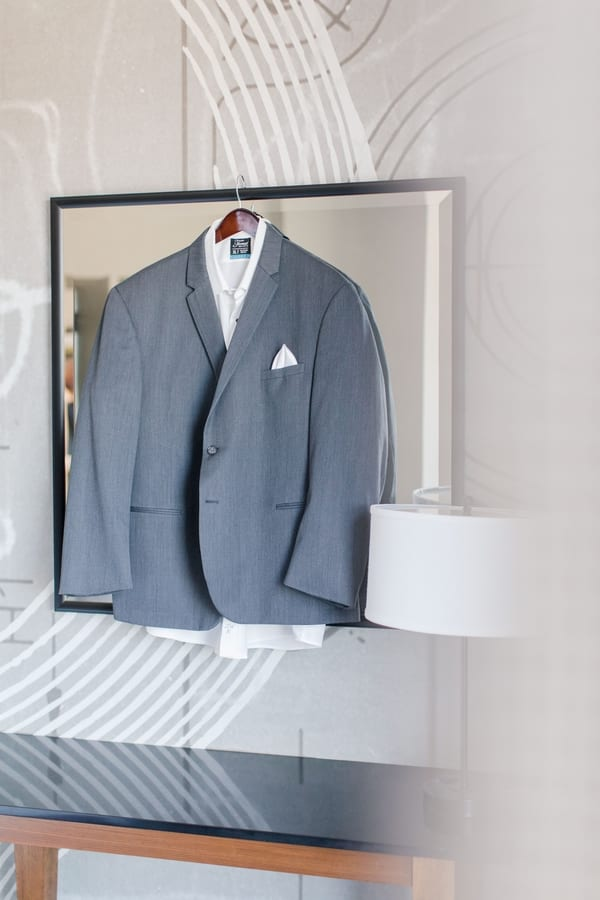 grey tuxedo hanging against a mirror on an art deco wall