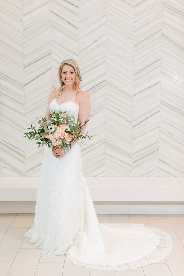 full length formal bridal portrait in front of white patterned wall