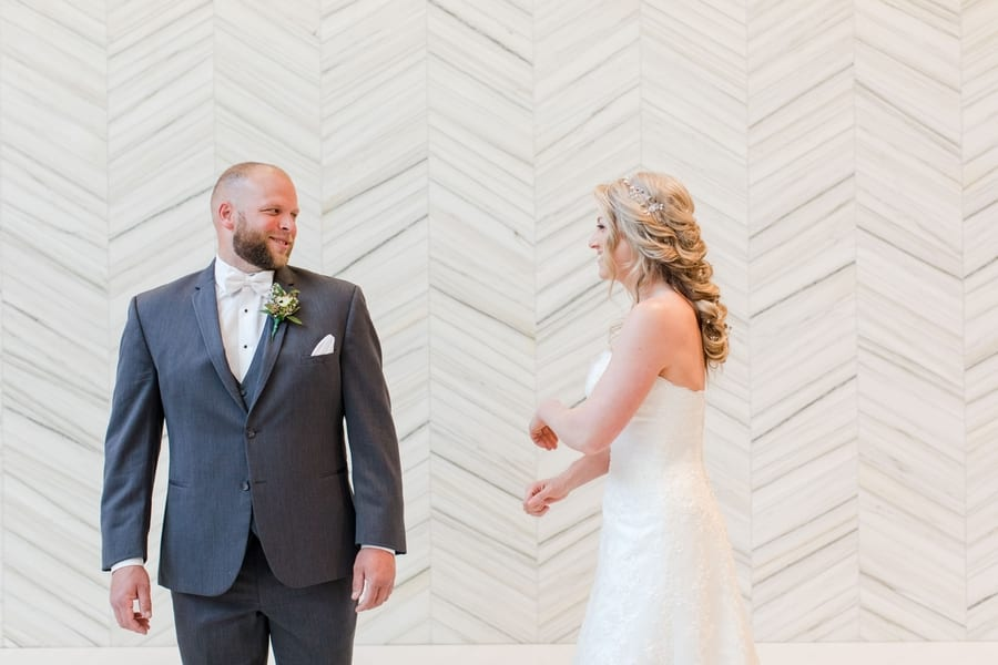 bride and groom laughing with one another during first look
