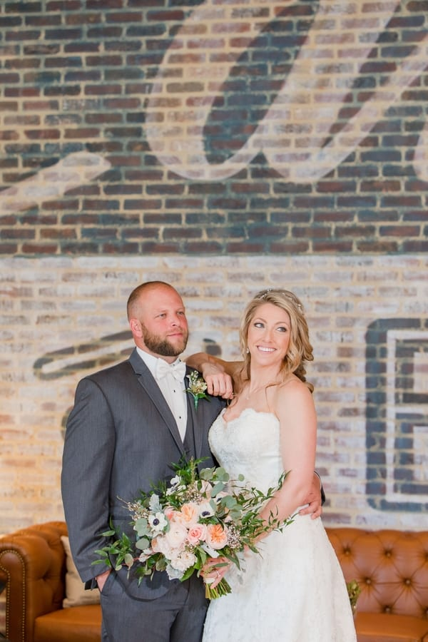 bride and groom portrait in front of painted tile wall in lobby of Embassy Suites hotel