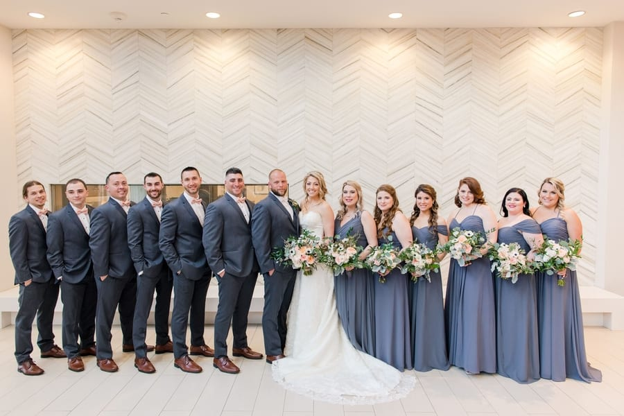 formal wedding party photo inside hotel lobby in front of white patterned wall
