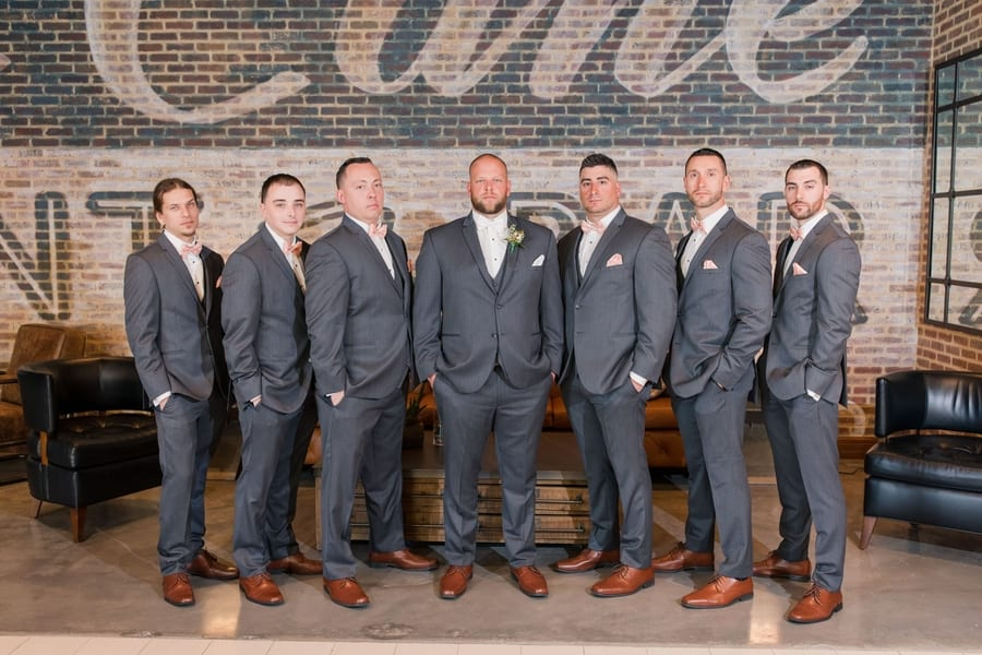 groom and his groomsmen in grey tuxedos with peach bowties in a formal serious photo in the lobby of the Embassy Suites in Berkeley Heights