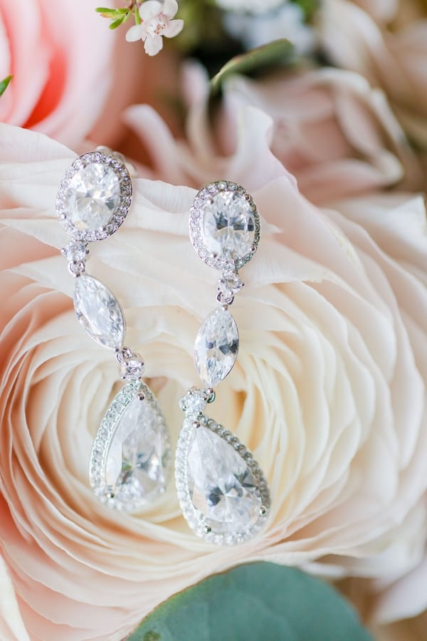 close up of brides dangling rhinestone earrings on a cream rose