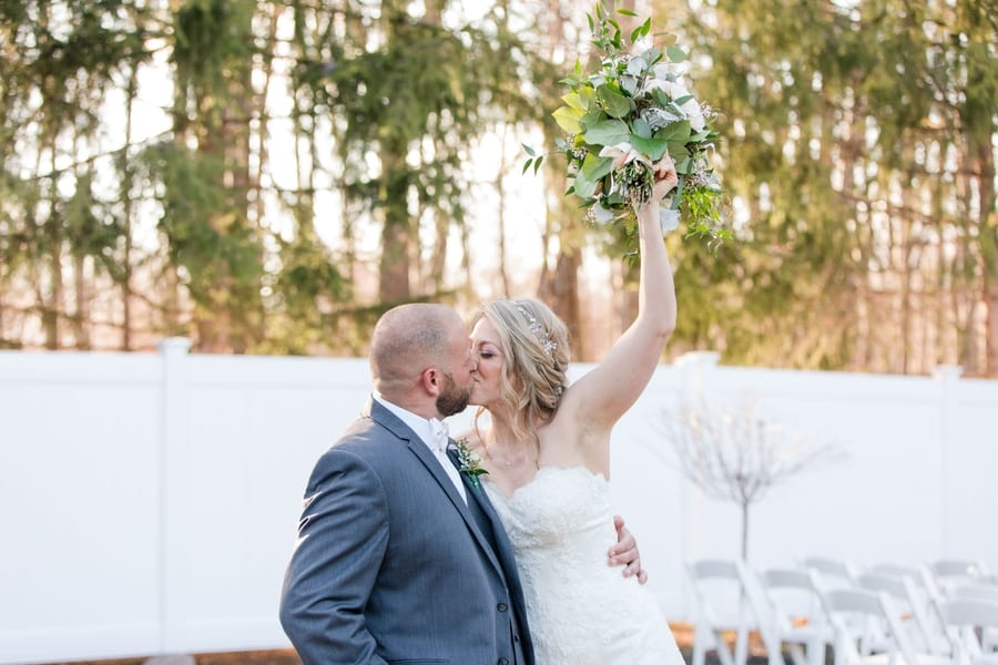 bride and groom portrait kissing with bouquet in the air