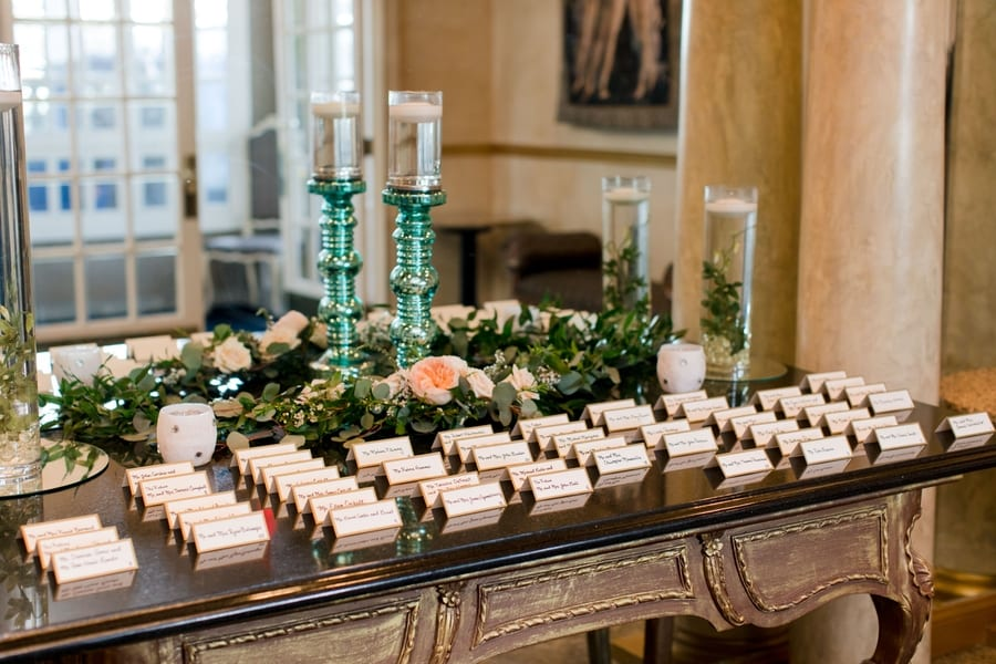 guest place cards on a side table in front of a mirror decorated with candles and greenery