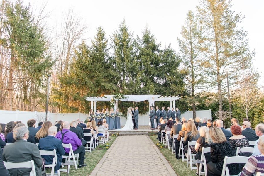 wide angle of bride and groom during ceremony with members of the wedding party on either side, under a fabric draped white pergola with the top left decorated with greenery and blush florals