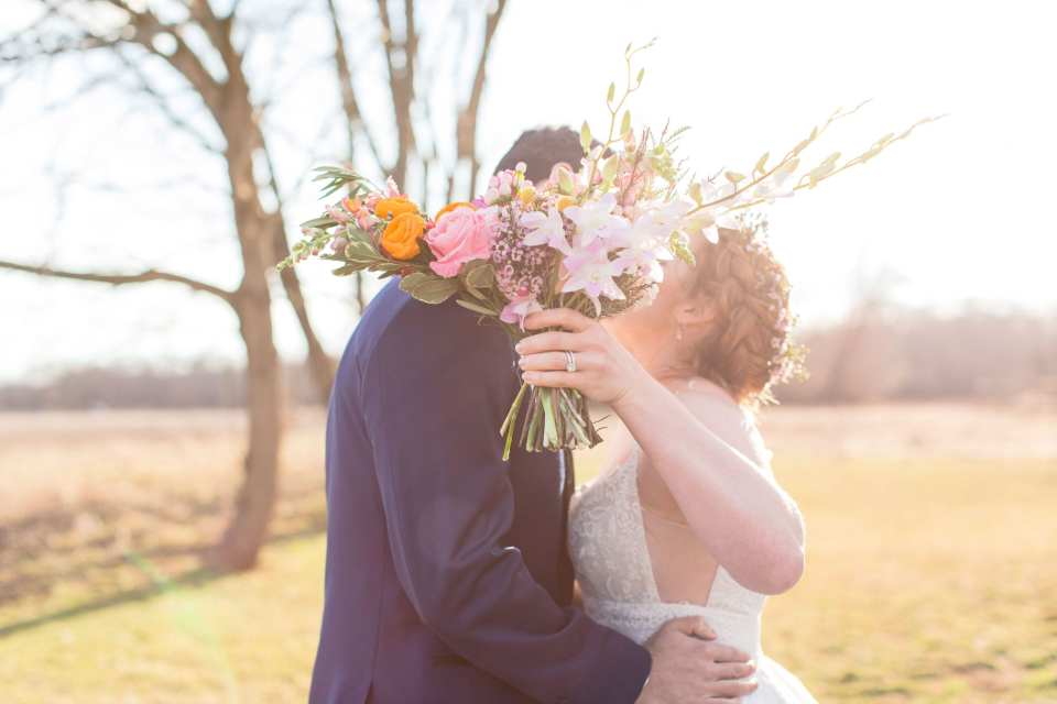 bride in spaghetti strap floral lace with crown of flowers in hair with her groom in a navy blue and black tuxedo with bridal bouquet of spring and wild flowers in front of their kissing faces