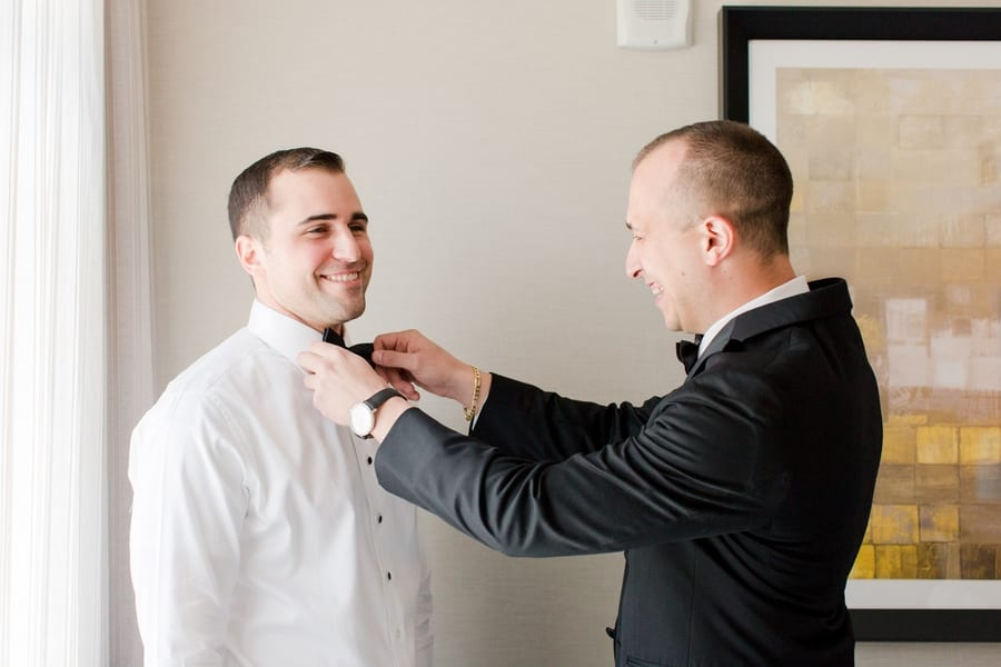 groom's bowtie being tied by a groomsman