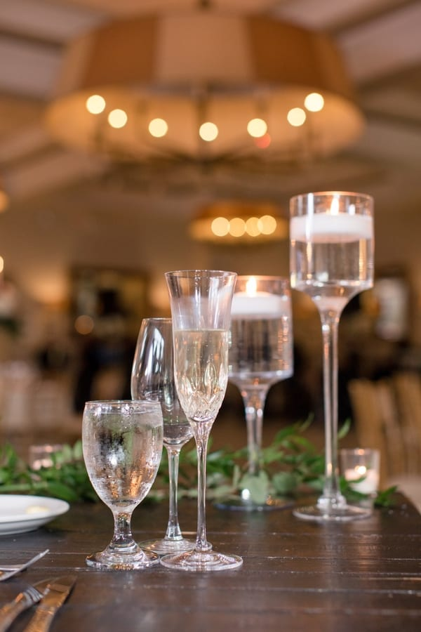 detail shot of champagne flute, wine and water glasses with glass floating candle holders