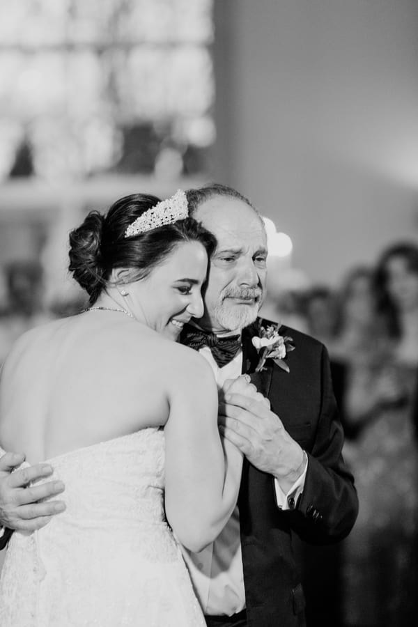 black and white candid photo of bride dancing with her father