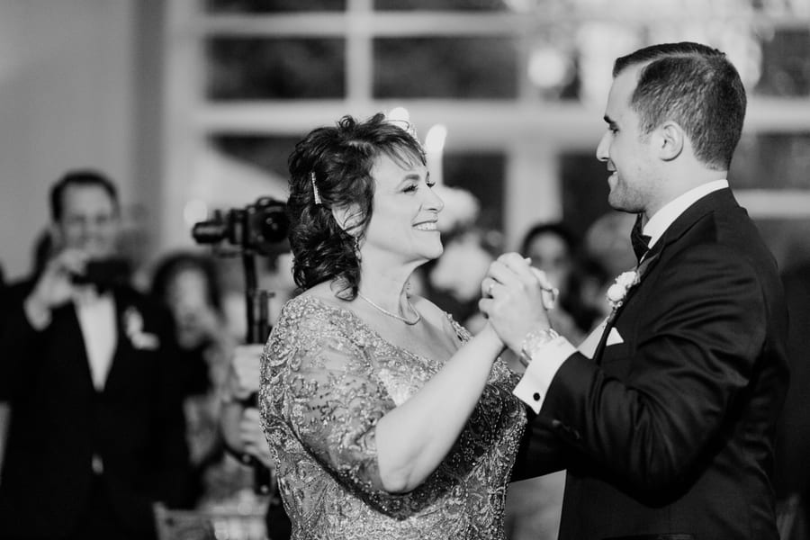 black and white candid photo of groom dancing with his mother