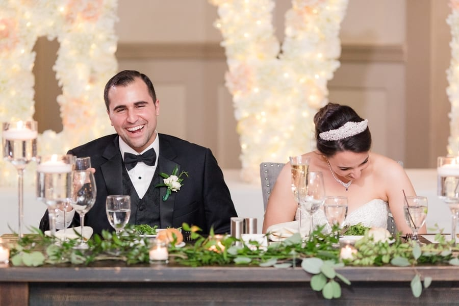 bride and groom laugh a lot during speeches and toasts while sitting at the sweetheart table together