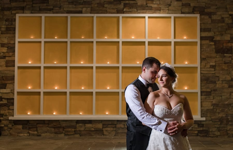 bride and groom outside wedding venue in front of paned window with tealights in each window pane
