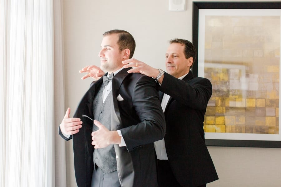 groom being helped into his tuxedo by his father
