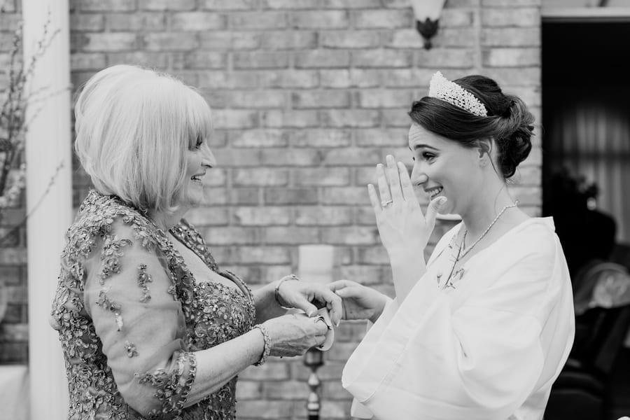 black and white photo of bride and her mother enjoying a tender moment together before getting into her wedding gown