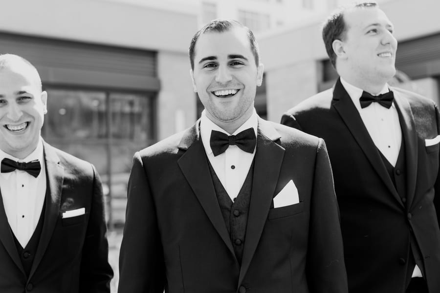 black and white candid photo of groom and a few of his grooms men