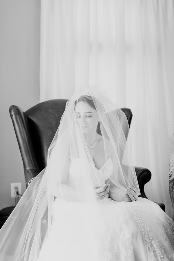 black and white photo of bride sitting in a wing back chair, looking serene, with veil over her face