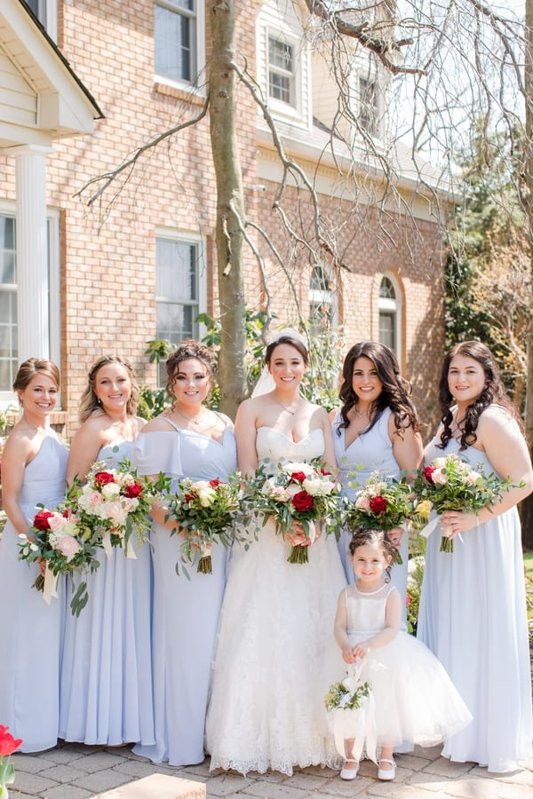 bride with her bridal party in powder blue, holding their bouquets