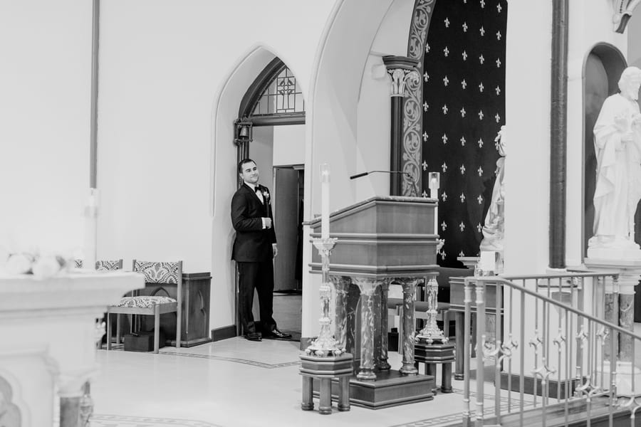 black and white candid photo of groom taking a peek from the side of the altar