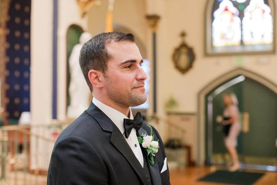 groom looking down the aisle as his bride makes her way down towards him
