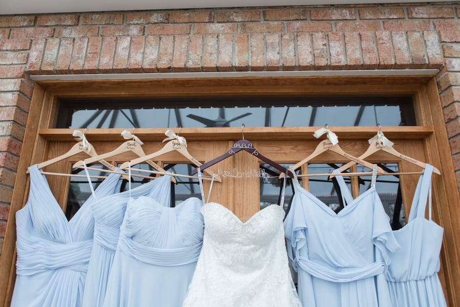 brides gown hanging on a personalized dark wooden hanger, displayed against a brick house, with the bridal party's powder blue gowns hung on personalized light wooden hangers