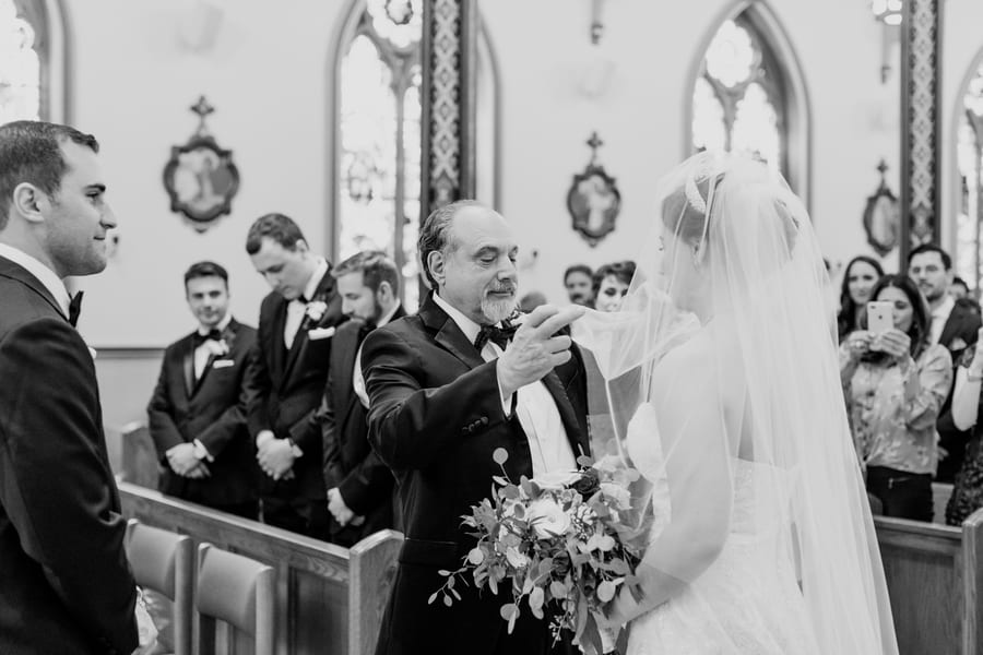 black and white candid photo of father of the bride lifing his daughters veil right before he hands her over to her groom