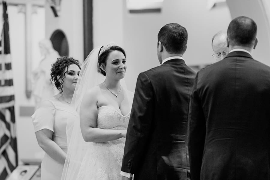 black and white photo of bride grinning at her husband while he says his vows