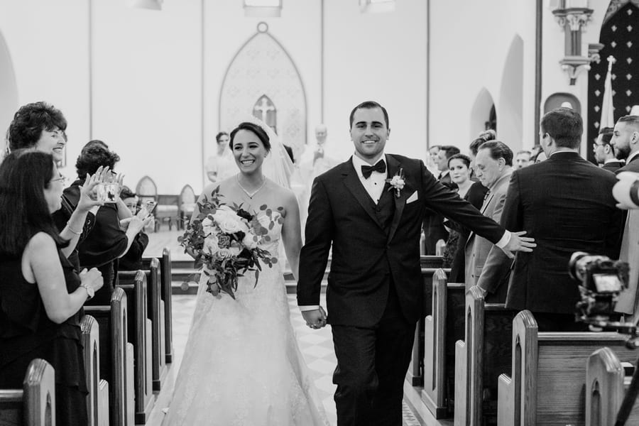 black and white photo of bride and groom walking back down the aisle of the church as Mr. and Mrs.