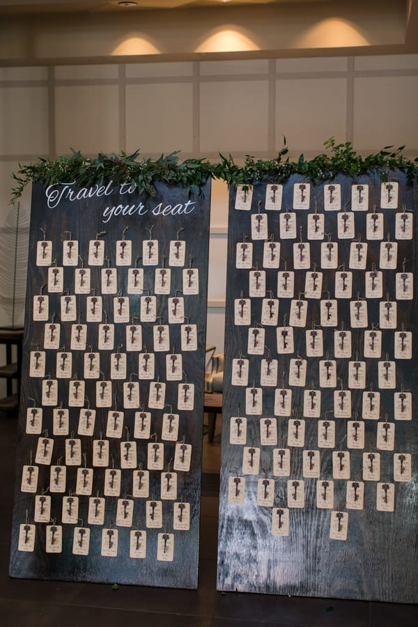 antique key and place cards on display on large wooden doors with greenery