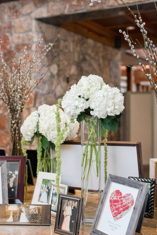 memory table display of family wedding photos with arrangements of white hydrangeas