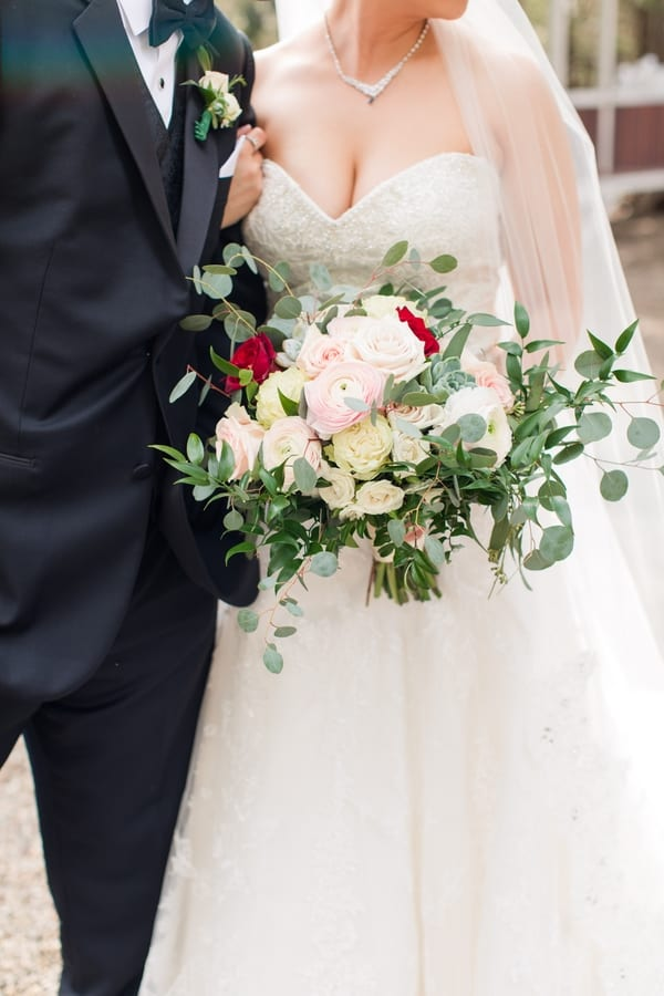 close up of bride holding her bridal bouquet of blush, cream and red roses, succulents and greenery