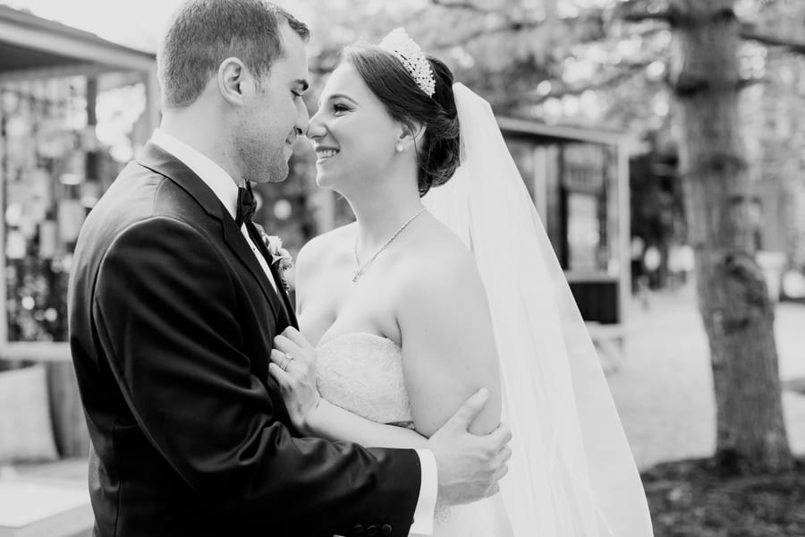 black and white candid photo of the bride and groom, with them touching their noses while smiling