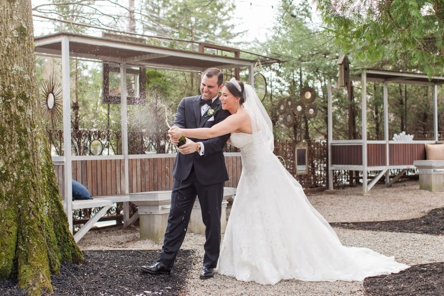 bride and groom popping champagne bottle outdoors on grounds of the Stone House