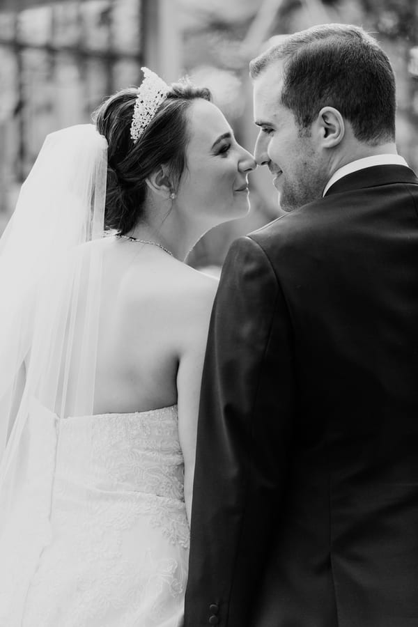 black and white candid photo from behind the bride and groom, with them touching their noses while smiling