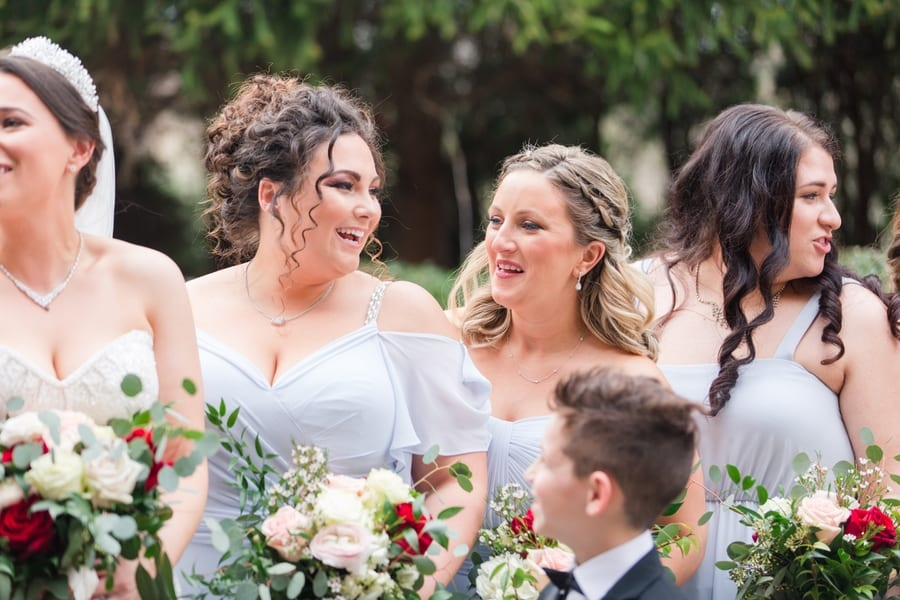 close up of members of the bridal party in powder blue sharing laughs during the wedding party photos