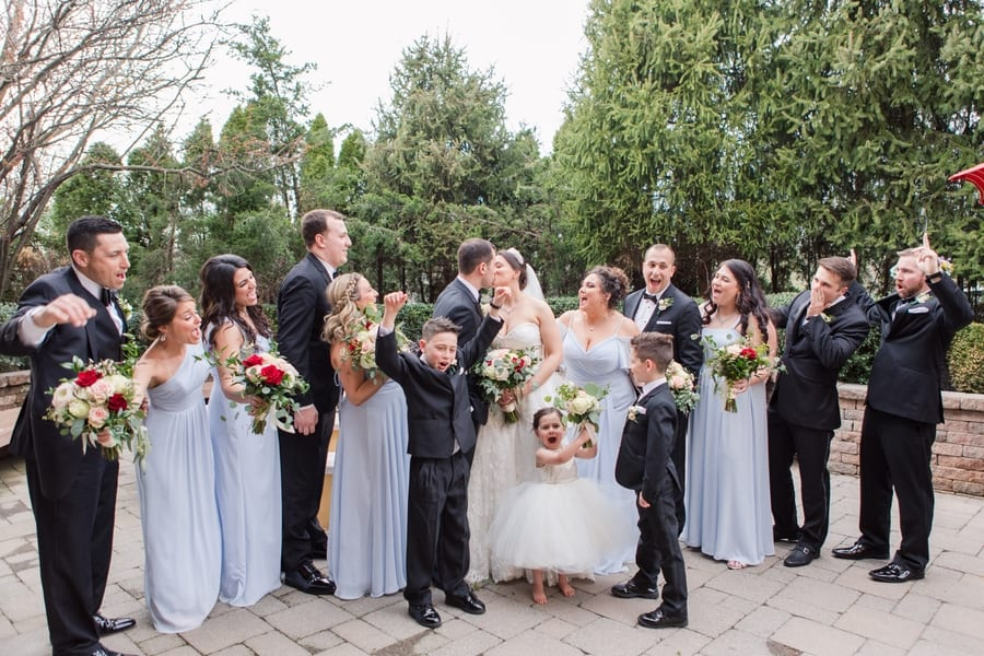 fun photo of entire wedding party cheering on the kissing bride and groom