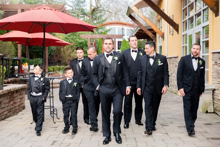 groom and his groomsmen candid shot of them walking outside the Stone House