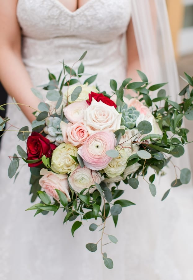 close up of bride holding her bridal bouquet of blush and red roses, pink and cream florals, succulents and greenery