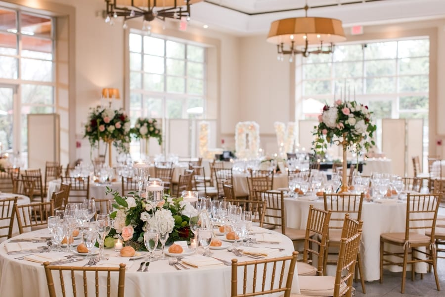 reception tables with tall and low floral arrangement in center of table, with place settings in places and gold chivari chairs