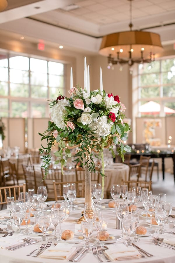 reception table with tall floral arrangement in center of table, with place settings in places and gold chivari chairs