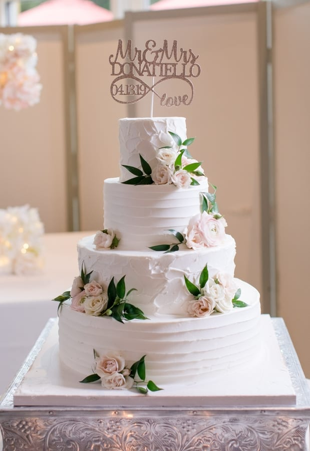 four tier whit wedding cake with two different frosting patterns with fresh blush florals scattered throughout the tiers with glittered cake topper of the bride and grooms name and wedding date
