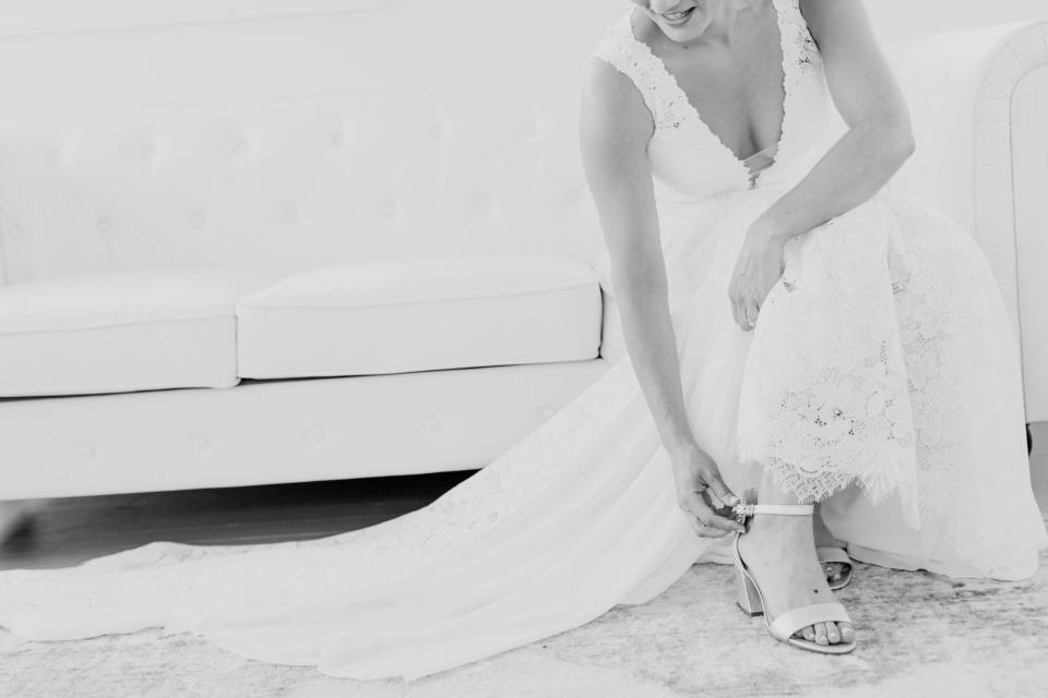 black and white photo of bride sitting on couch buckling her shoes