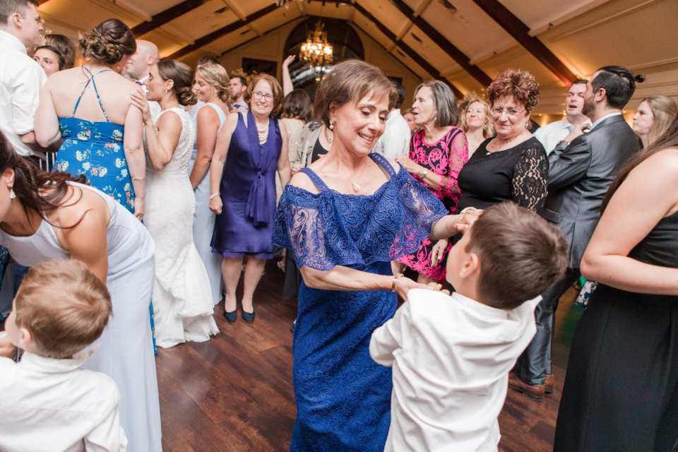 Mother of the bride dances with a young guest during the wedding reception