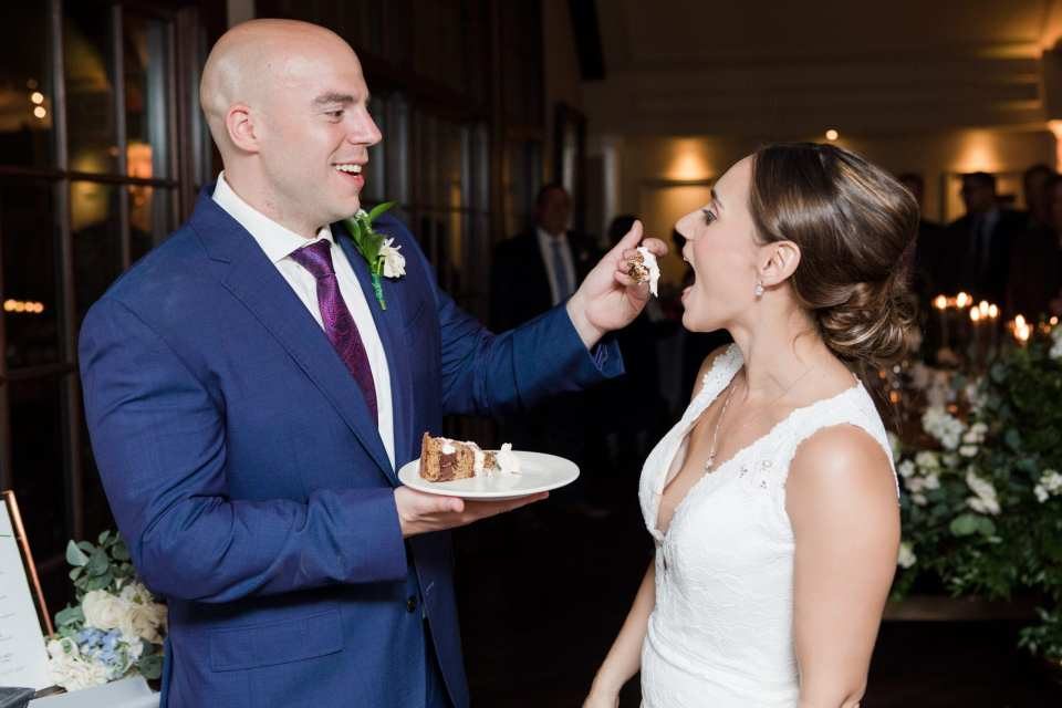 Groom in navy blue suit by Jos. A. Banks feeds his bride some of their wedding cake during the cake cutting. Bride in Pronovias, cake by Sweet Spot Bake Shoppe