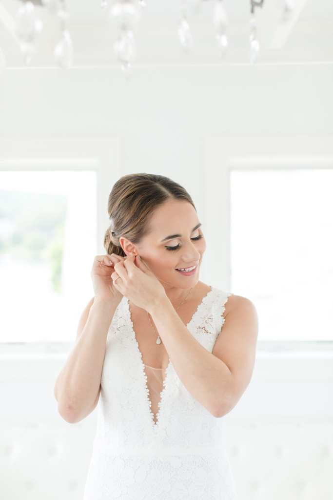 bride in lace vneck gown by Pronovias putting in her earring