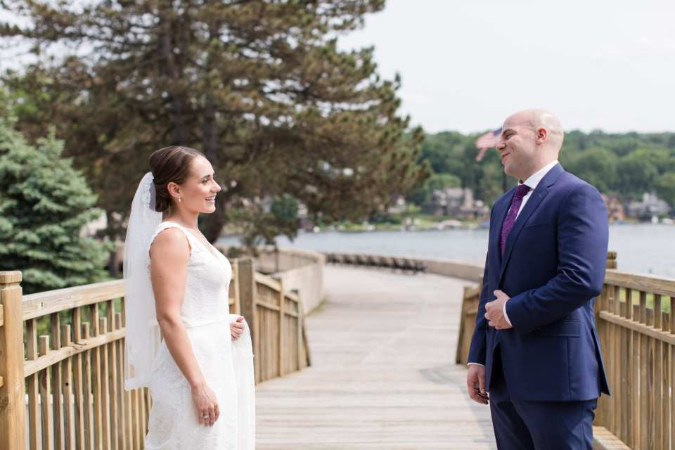 Bride and groom outdoors on the boardwalk of the Lake Mohawk Country Club seeing each other for the first time during their first look. Bride in Pronovias lace gown, Groom in navy blue suit