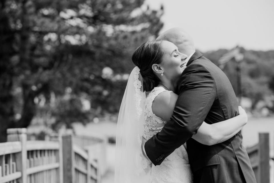 black and white candid photo of the bride and groom embracing during the first look outdoors at the Lake Mohawk Country Club