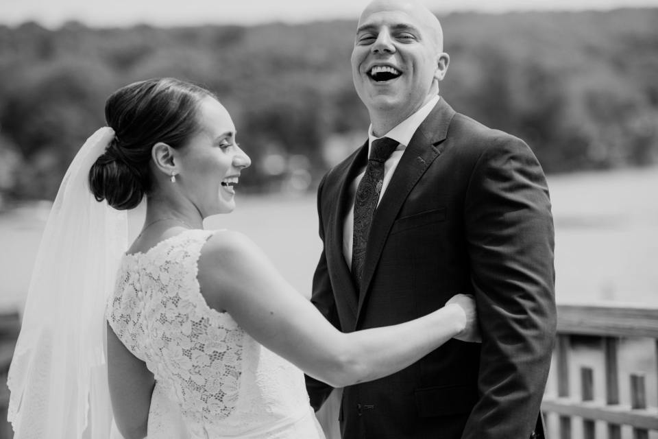 black and white candid photo of the bride and groom laughing, detail of the back of the lace gown by Pronovias